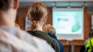 Mies kuuntelee kutsuntojen tilaisuudessa ohjeita Kuopiossa.