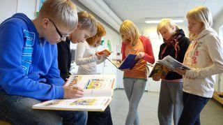 Melalahden koulun 6-luokkalaiset lukevat koulukirjaston kirjoja.