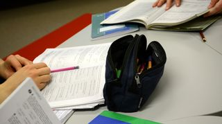 Penaali ja kirjoja opiskelijoiden käytössä pöydällä.