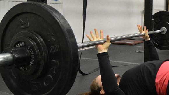 Nainen nostaa painoa.