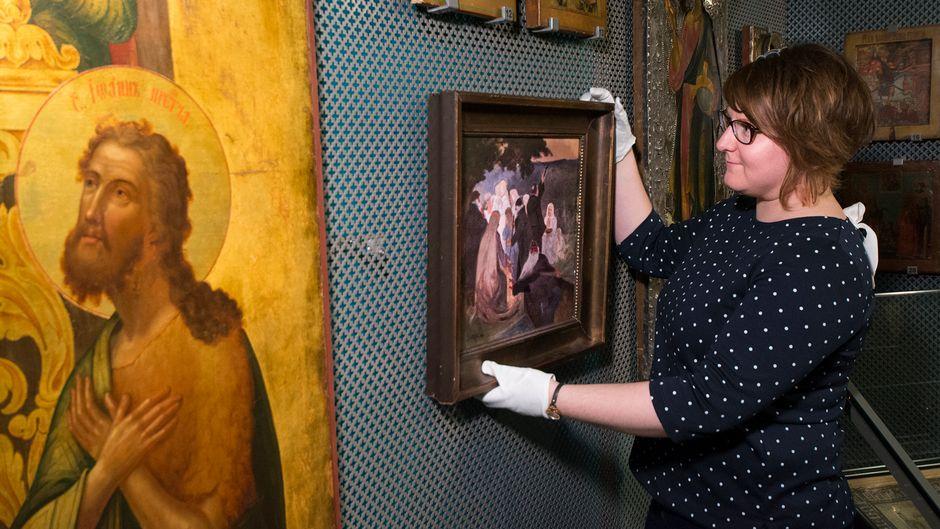 Amanuenssi Henna Hietainen ripustaa taulua ortodoksisen kirkkomuseon Riisan näyttelyssä