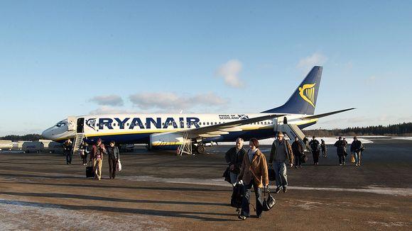 Matkustajia ja Ryanairin kone Tampere-Pirkkalan lentokentällä.