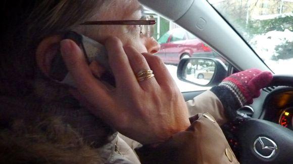 Nainen kännykkä korvalla auton ratissa.