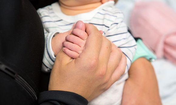Äiti pitelee kädestä vastasyntynyttä vauvaa sairaalassa.