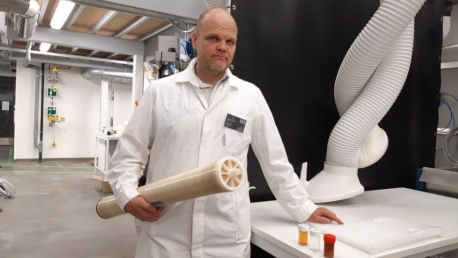 Professori Mika Mänttäri pitää kädessään membraanisuodatinta.
