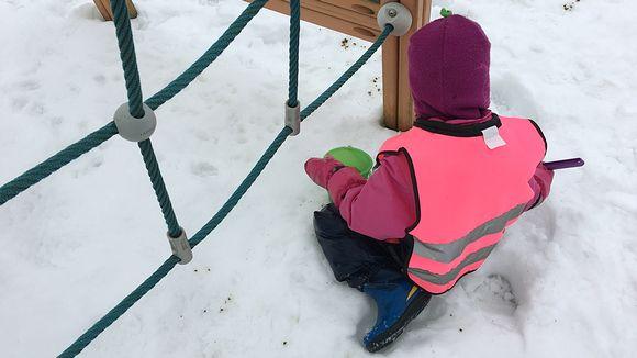 Lapsi leikkii lumessa.