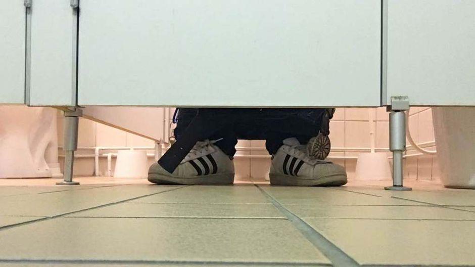 WC:n pöntöllä istuva henkilö