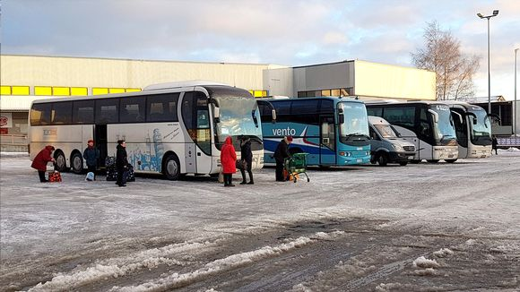 Venäläisiä busseja Prisman parkkipaikalla. Venäläisiä turisteja ostoskasseineen ulkopuolella.
