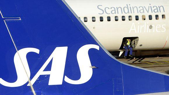 Työntekijä istuu SAS:n lentokoneen lastiluukulla Arlandan lentokentällä.