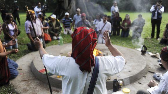 Shamaani suorittaa rituaalia tulen vieressä, ympärillä ihmisiä.