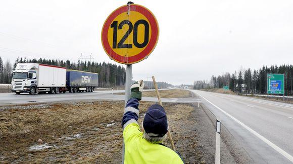 Tielaitoksen työntekijä vaihtaa nopeusrajoitusmerkkejä moottoritien varressa.
