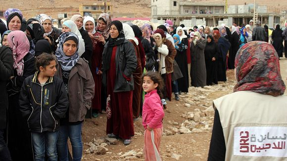 Syyrialaisia pakolaisia jonossa.