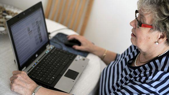Iäkäs nainen käyttää tietokonetta kotonaan.
