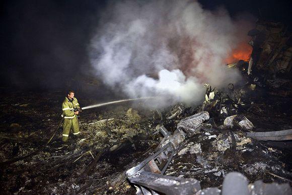 Palomiehet sammuttavat palavaa koneen runkoa.
