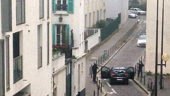 Aseistetut hyökkääjät ja poliisi vastakkain kadulla Charlie Hebdon toimitukseen kohdistuneen hyökkäyksen aikana.