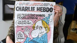 Henkilö näyttää ranskalaisen satiirisen sanomalehden Charlie Hebdon etusivua.