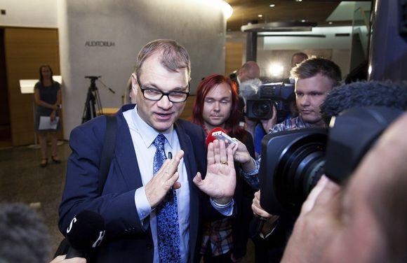 Pääministeri Juha Sipilä puhuu toimittajille saapuessaan suuren valiokunnan kokoukseen eduskunnan Piukuparlamentissä Helsingissä sunnuntaina 12. heinäkuuta.