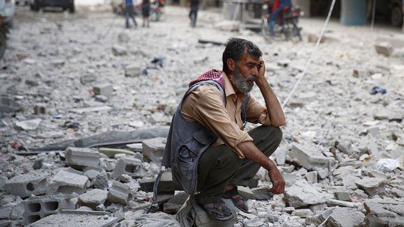 Syyrialaismies istuu Douman kaupungin raunioissa hallituksen joukkojen tekemän ilmaiskun jälkeen. Kuva on otettu 30. elokuuta. Jopa 240 000 ihmisen arvioidaan kuolleen Syyrian sodassa.