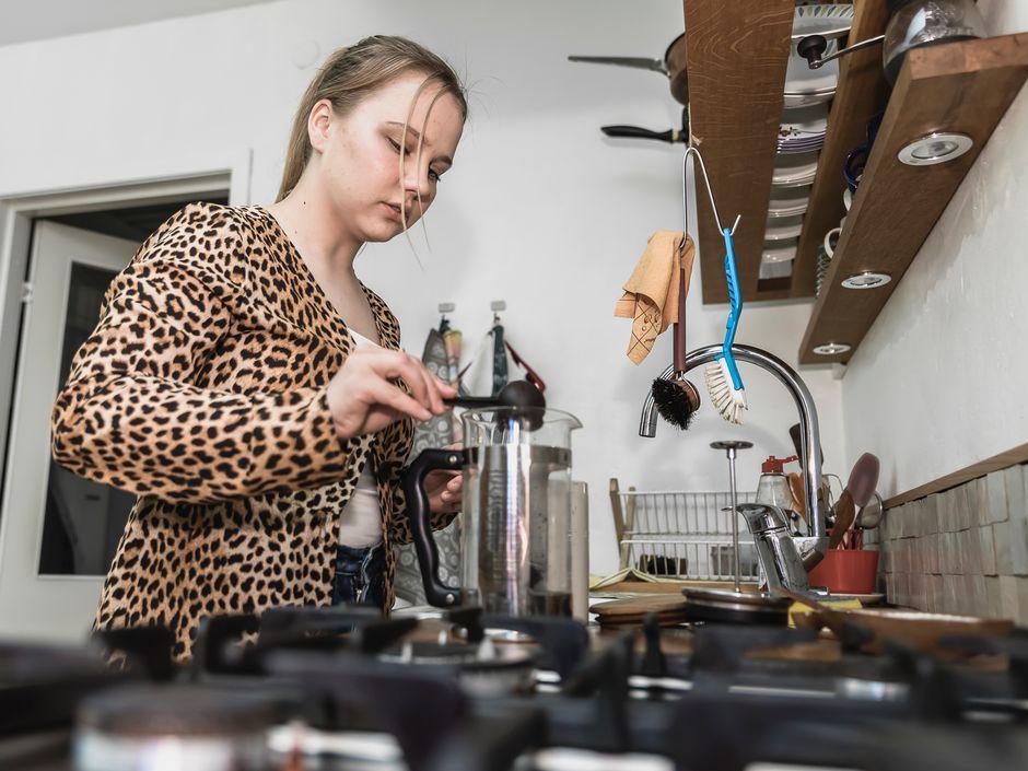 Amalia Paananen laittaa kahvinpuruja kahvinkeittimeen.