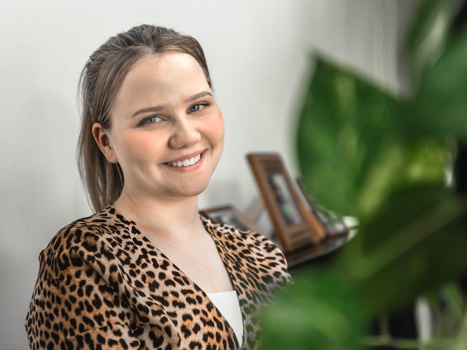 Amalia Paananen katsoo hymyille kameraan. Hänellä tukka ponnarilla ja leopardikuosinen vaate yllään.