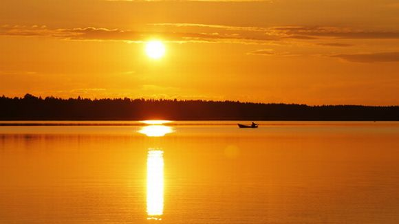 laskeva aurinko heijastuu järven pintaan