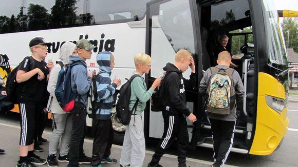 Koululaisia nousemassa bussiin.
