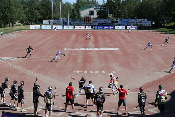 The pitcher throws the ball up, the batter swings, and the fielders must try to anticipate which direction the ball will go as Joensuu bat against Vimpeli in June 2018.
