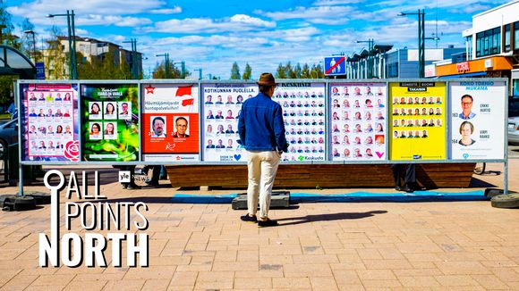 Photo of man looking at municipal election posters in Tornio, featuring All Points North podcast logo.