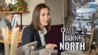 Prime Minister Sanna Marin (SDP) photographed at a cafe in Helsinki, featuring the All Points North podcast logo.