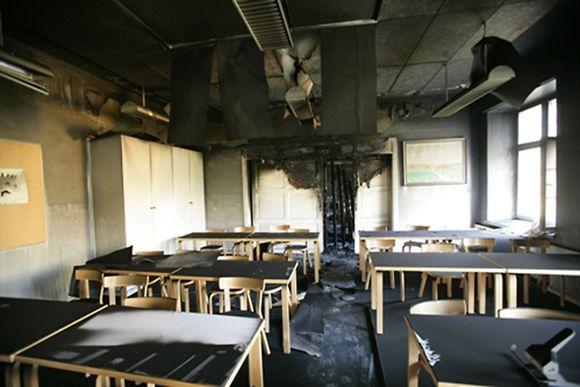 Luokkahuoneen katto ja seinät ovat osittain palaneet ja mustuneet.