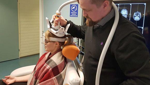 Dr. Aleksi Sihvonen stimulates researcher Sini Hämeläinen's brain magnetically.