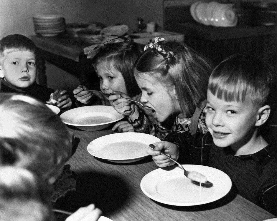 Oppilaat syövät kouluateriaa kansakoulussa.
