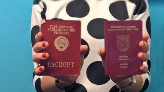 Nainen pitelee käsissään Suomen ja Venäjän passeja.