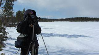 Kuvaaja ja kamera, taustalla kaukoputki