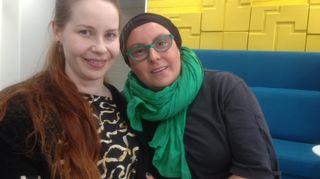 Kaksi naista istuu lähekkäin ja hymyilee