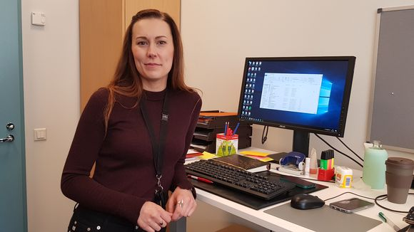 Nainen seisoo työpöydän ääressä.