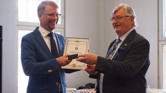Suomi-Seuran puheenjohtaja Jarmo Virmavirta (oikealla) ojensi palkinnon Mika Keräselle Helsingissä.