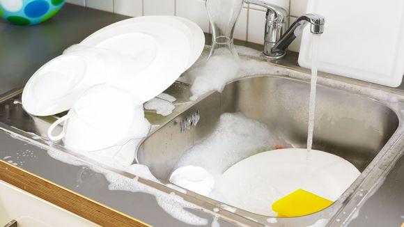 Hanasta valuu vettä tiskialtaaseen, jossa on astioita.
