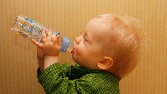 Pikkulapsi juo vettä tuttipullosta.