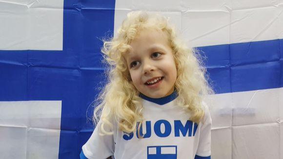 Suomi-paitainen lapsi haastateltavana Suomen lipun edessä.