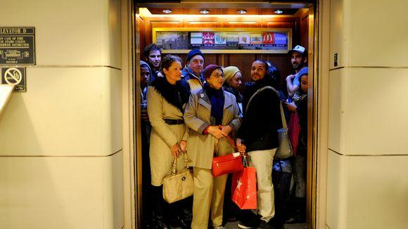 Paljon ihmisiä hississä.