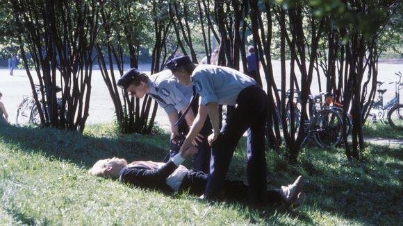 Kaksi poliisia yrittää herättää humalaista miestä, joka nukkuu puistossa.