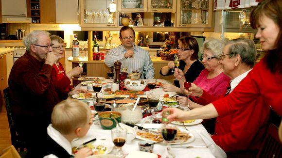 Ihmisiä syömässä joulupöydässä.