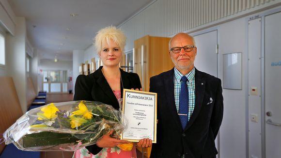 Mies ja nainen, jolla on kädessä kunniakirja ja kukkia.