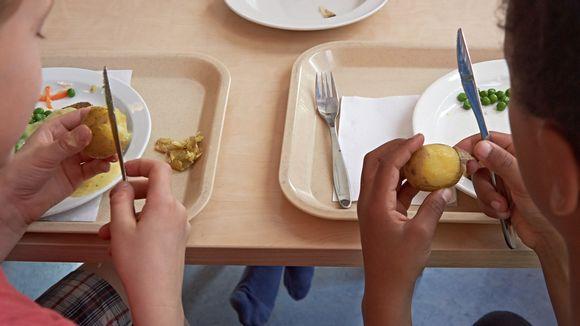 Lapset kuorivat perunoita.