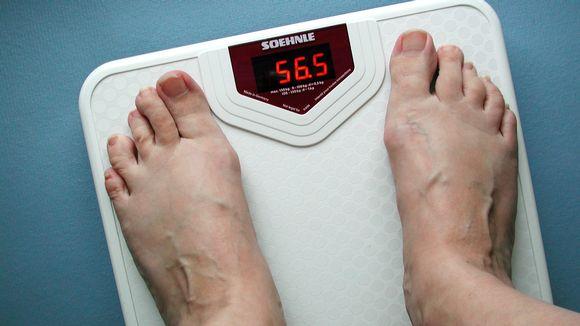 Naisen jalat vaa'alla, jokä näyttää lukemaa 56,5 kiloa.