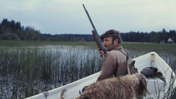 Mies istuu veneessä metsästysase kädessä ja koira vierellä.