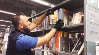 Mies laittaa kirjaa hyllyyn kirjastossa.