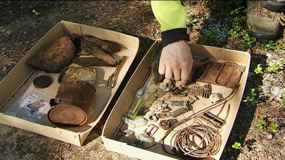 Kädet harovat esineitä laatikossa.