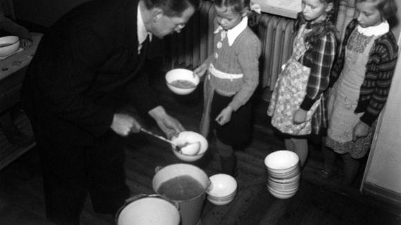 Opettaja jakaa keittoa oppiilaille. Oppilaat seisovat jonossa odottamassa vuoroaan.